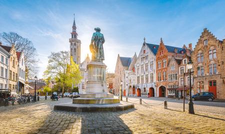 Scenic view of historical Brugge city center with famous Jan van Eyck square in beautiful golden evening light, Flanders region, Belgium