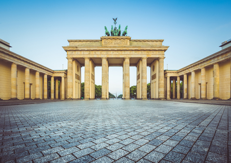 Famous Brandenburger Tor (Brandenburg Gate), one of the best-known landmarks and national symbols of Germany, in beautiful golden morning light at sunrise with retro vintage style pastel toned filter effect, Berlin, Germany Stock fotó