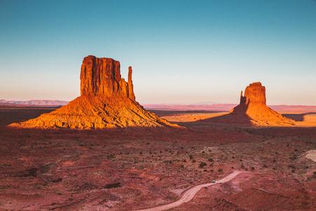 Vista clásica del famoso Monument Valley con la sombra del West Mitten que se proyecta sobre el East Mitten en la hermosa luz dorada del atardecer al atardecer, Arizona, EE. Foto de archivo