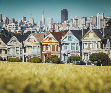 Classic postcard view of famous Painted Ladies, a row of colorful Victorian houses located at Alamo Square, with the skyline of San Francisco in the background Stockfoto