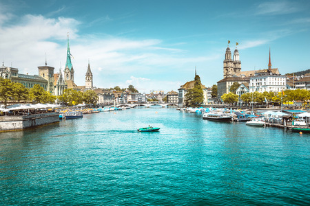 Panoramic view of Zurich city center with churches and boats on beautiful river Limmat in summer, Canton of Zurich, Switzerland Banco de Imagens