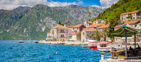Scenic panorama view of the historic town of Perast at famous Bay of Kotor on a beautiful sunny day with blue sky and clouds in summer, Montenegro, southern Europe