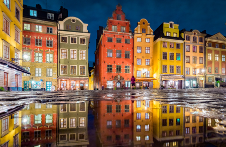 Classic view of colorful houses at famous Stortorget town square in Stockholms historic Gamla Stan (Old Town) reflecting in a puddle at night, central Stockholm, Sweden