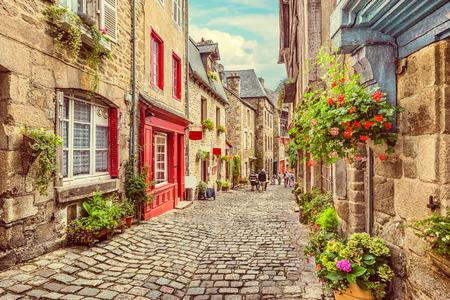 Splendida vista del pittoresco vicolo stretto con case tradizionali storiche e strada acciottolata in una città vecchia in Europa con cielo azzurro e nuvole in estate con effetto filtro grunge vintage retrò