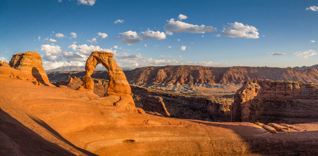Classic panorama view of famous Delicate Arch, symbol of Utah and a popular scenic tourist attraction, in beautiful golden evening light at sunset in summer, Arches National Park, Moab, Utah, USA