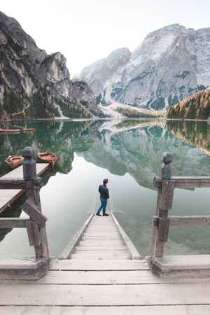 Beautiful view of a young man standing on wooden stairs watching the sunrise at famous Lago di Braies the Dolomites, South Tyrol, Italy Stock Photo