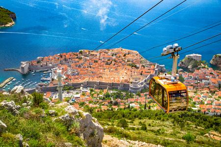 Vista panorámica aérea del casco antiguo de Dubrovnik con el famoso teleférico en la montaña Srd en un día soleado con cielo azul y nubes en verano, Dalmacia, Croacia