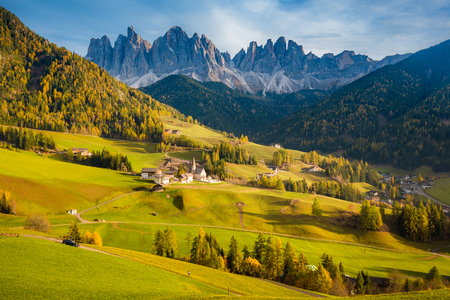 Beautiful view of idyllic mountain scenery in the Dolomites with famous Santa Maddelana mountain village in beautiful golden evening light at sunset in fall, Val di Funes, South Tyrol, northern Italy.