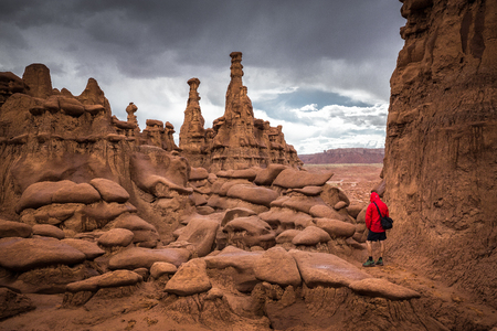 Panoramic view of hiker in red jacket standing in Goblin Valley State Park amidst beautiful hoodoos sandstone formations, Utah, USA