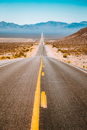 Classic panorama view of an endless straight road running through the barren scenery of the American Southwest with extreme heat haze on a beautiful sunny day with blue sky in summer Stockfoto