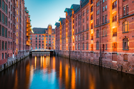 Classic view of famous Speicherstadt warehouse district, illuminated in beautiful post sunset twilight at dusk, Hamburg, Germany Stock Photo