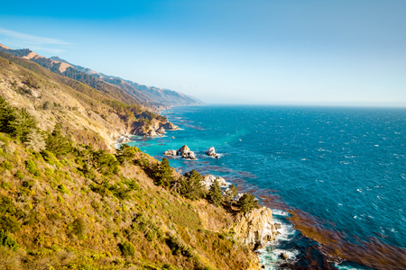 Scenic view of the rugged coastline of Big Sur with Santa Lucia Mountains along famous Highway 1 illuminated in beautiful golden evening light at sunset in summer, California Central Coast, USA 写真素材