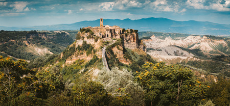 Beautiful view of famous Civita di Bagnoregio with Tiber river valley and dramatic cloudscape at sunset, Lazio, Italy