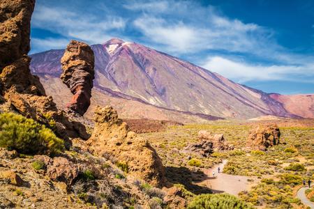 Panoramiczny widok na unikalną formację skalną Roque Cinchado ze słynnym szczytem wulkanu Pico del Teide w tle w słoneczny dzień, Park Narodowy Teide, Teneryfa, Wyspy Kanaryjskie, Hiszpania