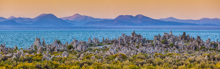 Panoramic view of fascinating tufa rocks at Mono Lake with Sierra Nevada mountain range in the background in beautiful evening light at sunset in summer, Mono County, California, USA