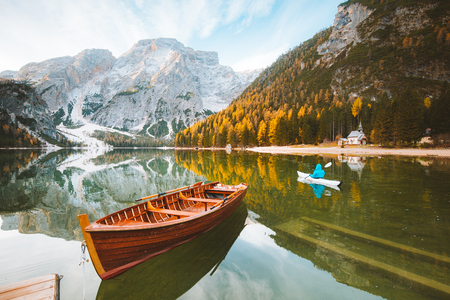 Beautiful view of famous Lago di Braies with traditonal rowing boat and young man in kayak at sunrise in fall, Dolomites, Italy Stock Photo