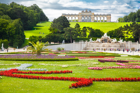 Classic view of famous Schonbrunn Palace with scenic Great Parterre garden on a beautiful sunny day with blue sky and clouds in summer, Vienna, Austria 新聞圖片