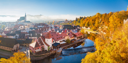 Panoramic view of the historic city of Cesky Krumlov, a UNESCO World Heritage Site since 1992, in beautiful golden morning light at sunrise with mystic fog in fall, Czech Republic
