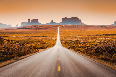 Classic panorama view of historic U.S. Route 163 running through famous Monument Valley in beautiful golden evening light at sunset in summer, Utah, USA Banco de Imagens - 121793576