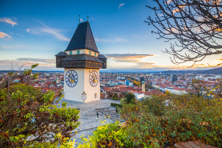 Classic panorama view of the historic city of Graz with famous Grazer Uhrturm clock tower in beautiful evening light at sunset, Styria, Austria Editorial