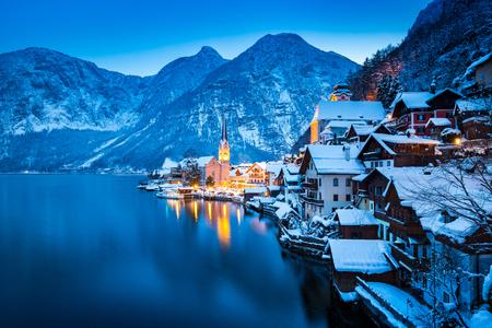 Klassieke ansichtkaartweergave van de beroemde Hallstatt-stad aan het meer in de Alpen met prachtige Hallstattersee in mystieke schemering na zonsondergang tijdens het blauwe uur in de schemering in de winter, Salzkammergut, Oostenrijk Stockfoto