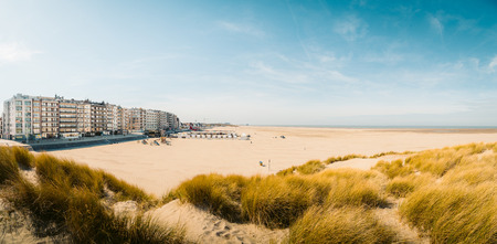 Beautiful panoramic of Zeebrugge beach with sand dunes and hotel buildings on a scenic sunny day with blue sky, Flanders, Belgium