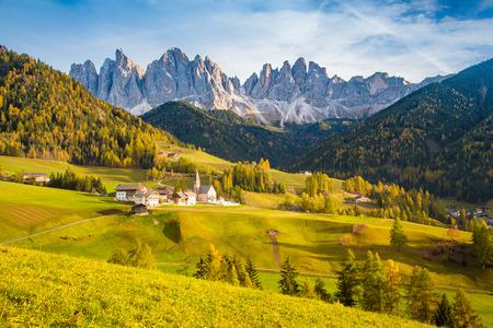 Schöne Ansicht der idyllischen Berglandschaft in den Dolomiten mit dem berühmten Bergdorf Santa Maddelana im schönen goldenen Abendlicht bei Sonnenuntergang im Herbst, Val di Funes, Südtirol, Norditalien. Standard-Bild