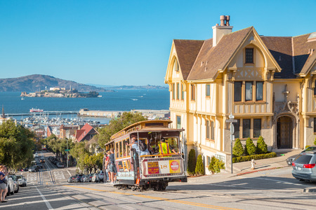SEPTEMBER 25, 2016 - SAN FRANCISCO: Powell-Hyde cable car climbing up steep hill in central San Francisco with famous Alcatraz Island in the background on a sunny day with blue sky, USA.