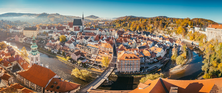 Aerial view of the historic city of Cesky Krumlov with famous Cesky Krumlov Castle, a UNESCO World Heritage Site since 1992, in beautiful golden morning light at sunrise with fog in fall, Czech Republic
