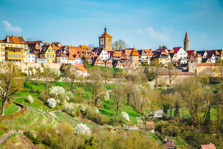Classic view of the medieval town of Rothenburg ob der Tauber on a beautiful sunny day with blue sky and clouds in springtime, Bavaria, Germany