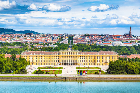 Classic view of famous Schonbrunn Palace with scenic Great Parterre garden on a beautiful sunny day with blue sky and clouds in summer, Vienna, Austria