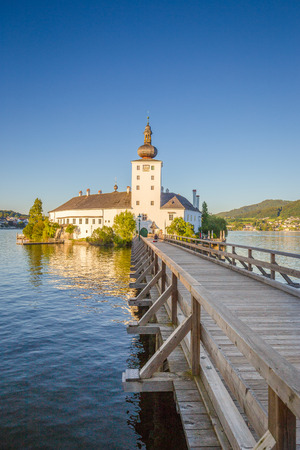 Beautiful view of famous Schloss Ort with wooden bridge at Lake Traunsee in beautiful golden evening light at sunset, Gmunden, Salzkammergut region, Austria