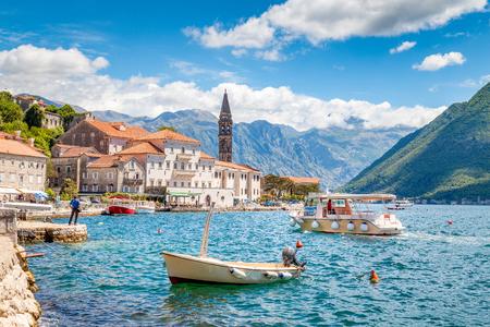 Malowniczy widok na panoramę zabytkowego miasta Perast położonego w słynnej na całym świecie Zatoce Kotorskiej w piękny słoneczny dzień z błękitnym niebem i chmurami w lecie, Czarnogóra, Europa Południowa
