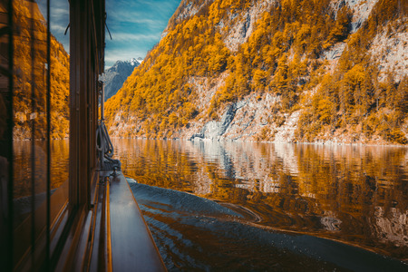 Traditional passenger boat gliding on Lake Konigssee with Watzmann mountain in the background on a beautiful sunny day in fall, Berchtesgadener Land, Bavaria, Germany Stock Photo