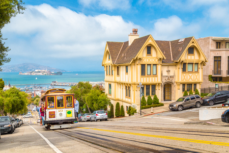 SAN FRANCISCO, USA - SEPTEMBER 3, 2016: Powell-Hyde cable car climbing up steep hill in central San Francisco with famous Alcatraz Island in the background on a sunny day with blue sky, USA.