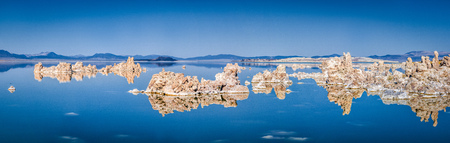 Panoramic view of fascinating tufa rock formations mirrored on calm water surface of famous Mono Lake on a beautiful sunny day with blue sky in summer, Mono County, California, USA