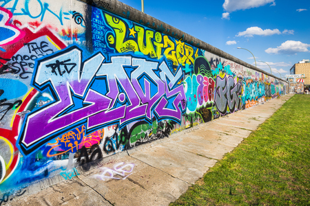 Panoramic view of famous Berlin Wall decorated with colorful graffiti street art at historic East Side Gallery on a sunny day with blue sky and clouds in summer, Berlin, Germany 新聞圖片