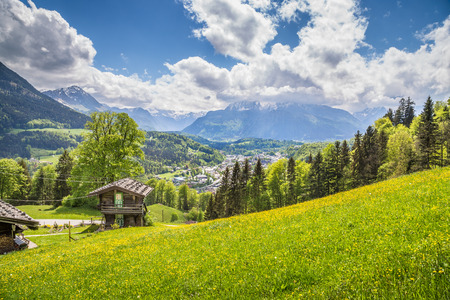 Panoramic view of idyllic mountain scenery in the Alps with traditional wooden mountain chalet and blooming meadows on a beautiful sunny day with blue sky and clouds in springtime