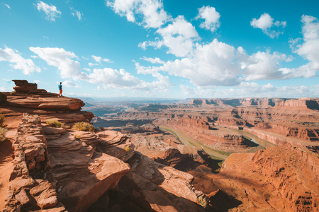 A young hiker is standing on the edge of a cliff enjoying a dramatic overlook of famous Colorado River and beautiful Canyonlands National Park in scenic Dead Horse Point State Park, Utah, USA