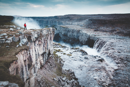Panorama view of hiker in red jacket standing in front of gigantic Dettifoss waterfall on a moody day with dark clouds in summer, Skogar, Iceland