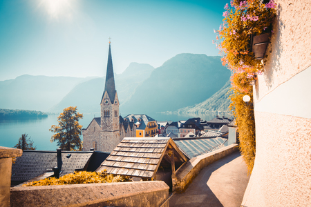 Classic postcard view of famous Hallstatt lakeside town in the Alps with historic church tower in scenic golden morning light on a beautiful sunny day in summer, Salzkammergut region, Austria