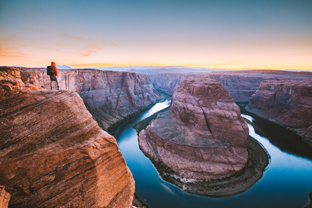 A male hiker is standing on steep cliffs enjoying the beautiful view of Colorado river flowing at famous Horseshoe Bend overlook in beautiful post sunset twilight on a summer evening, Arizona, USA Banco de Imagens - 121795311