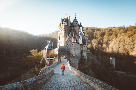 Panorama view of young explorer with backpack taking in the view at famous Eltz Castle at sunrise in fall, Rheinland-Pfalz, Germany Editorial