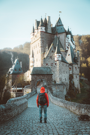 Panorama view of young explorer with backpack taking in the view at famous Eltz Castle at sunrise in fall, Rheinland-Pfalz, Germany Redactioneel