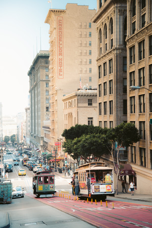 Traditional Powell-Hyde cable cars riding in central San Francisco in beautiful golden evening light at sunset, California, USA Stock fotó