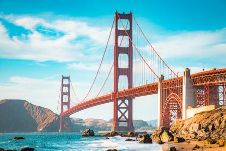 Klasyczny widok słynnego mostu Golden Gate w pięknym złotym wieczornym świetle w słoneczny dzień z niebieskim niebem i chmurami w lecie, San Francisco, Kalifornia, USA