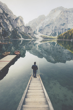 Beautiful view of a young man standing on wooden stairs watching the sunrise at famous Lago di Braies the Dolomites, South Tyrol, Italy Stock Photo - 121795429
