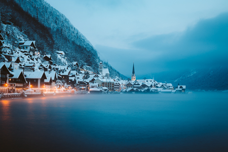 Panorama view of famous Hallstatt lakeside town in the Alps in mystic twilight during blue hour at dawn on a beautiful cold foggy day in winter, Salzkammergut region, Austria Stock Photo - 121795455
