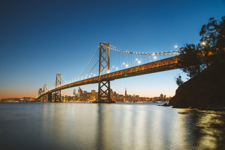 Classic panoramic view of San Francisco skyline with famous Oakland Bay Bridge illuminated in beautiful evening twilight at dusk in summer, San Francisco Bay Area, California, USA
