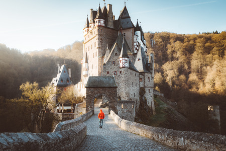 Panorama view of young explorer with backpack taking in the view at famous Eltz Castle at sunrise in fall, Rheinland-Pfalz, Germany Éditoriale